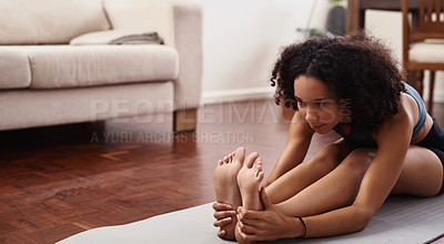 Buy stock photo Shot of a young woman stretching during her workout routine at home
