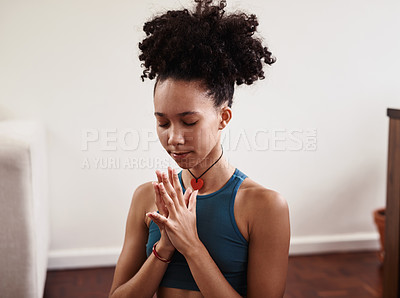 Buy stock photo Shot of a fit young woman meditating at home