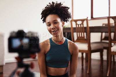 Buy stock photo Shot of a young woman recording herself doing yoga at home