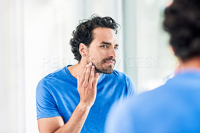 Buy stock photo Cropped shot of a handsome young man examining his face in the bathroom mirror