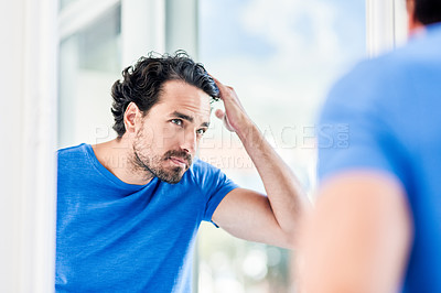 Buy stock photo Cropped shot of a handsome young man styling his hair inside his bathroom at home