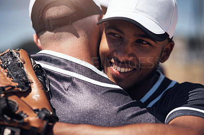 Buy stock photo Shot of two young men embracing after playing a game of baseball