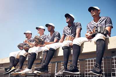 Buy stock photo Shot of a group of young men sitting on top of the dugout and watching a baseball game