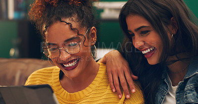 Buy stock photo Shot of two friends using a digital tablet while sitting on a couch
