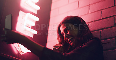 Buy stock photo Shot of a young woman taking a selfie while standing outside a building at night
