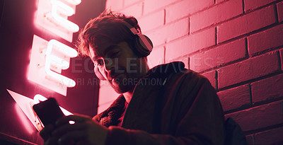 Buy stock photo Shot of a man wearing his headphones while using his cellphone outside a building