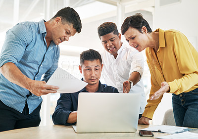 Buy stock photo Shot of a young businessman surrounded by demanding colleagues while working at his desk in an office