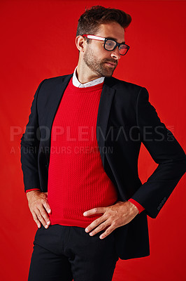 Buy stock photo Studio shot of a handsome and stylish young man posing with his hands on his hips against a red background