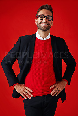 Buy stock photo Studio portrait of a handsome and stylish young man posing with his hands on his hips against a red background