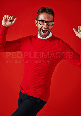 Buy stock photo Studio portrait of a handsome and stylish young man cheering against a red background