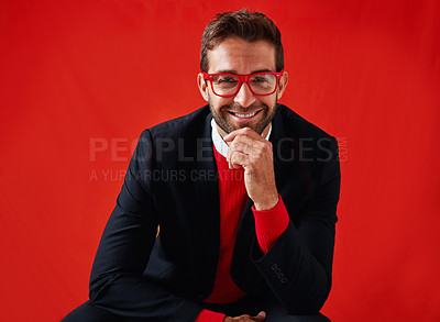 Buy stock photo Studio portrait of a handsome and stylish young man looking thoughtful against a red background