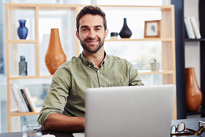 Buy stock photo Cropped portrait of a handsome young businessman working on his laptop in the office