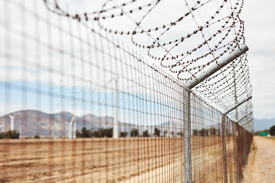 Buy stock photo Shot of a barbed wire fence surrounding a wind turbine farm