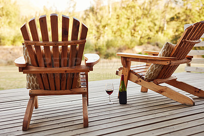 Buy stock photo Shot of wine and wooden chairs on a deck out in a garden
