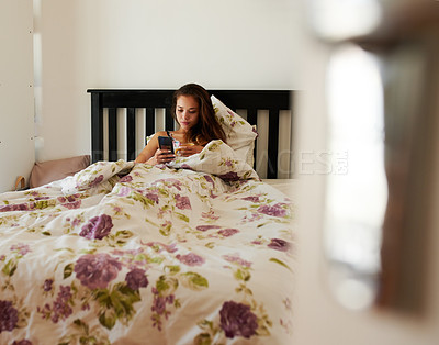 Buy stock photo Shot of a young woman using her cellphone while lying in her bed