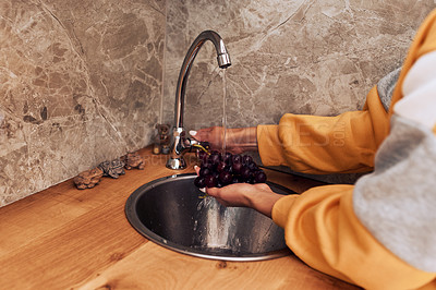 Buy stock photo Cropped shot of an unrecognizable woman rinsing grapes in her kitchen sink