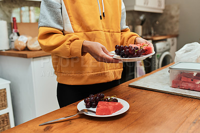 Buy stock photo Shot of an unrecognizable woman placing fruit in plates at home