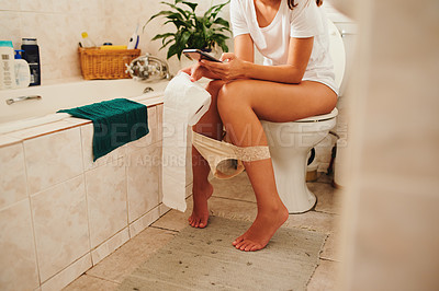 Buy stock photo Cropped shot of an unrecognisable woman sitting on the toilet and using a smartphone at home