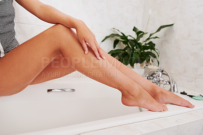 Buy stock photo Cropped shot of a woman's legs as she goes through her morning beauty routine at home