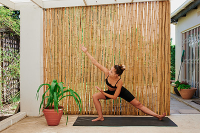 Buy stock photo Shot of a young woman practicing the warrior pose during a yoga session at home