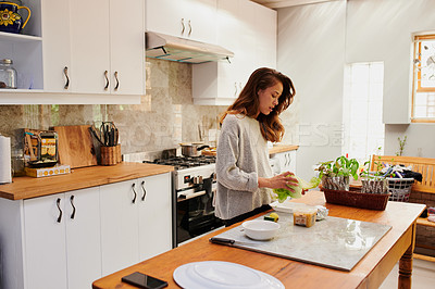 Buy stock photo Shot of a young woman preparing a healthy meal at home