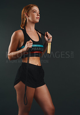 Buy stock photo Studio shot of a sporty young woman posing with a skipping rope against a black background