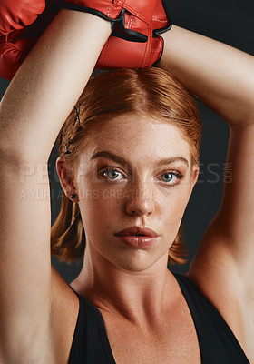 Buy stock photo Studio portrait of a sporty young woman wearing boxing gloves against a black background
