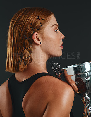 Buy stock photo Studio shot of a sporty young woman holding a trophy against a black background