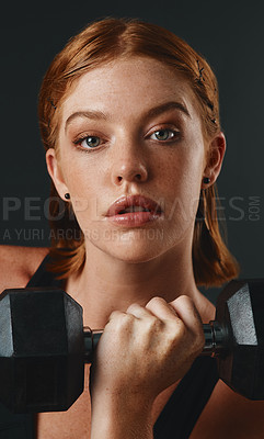 Buy stock photo Studio portrait of a sporty young woman exercising with a dumbbell against a black background