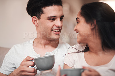 Buy stock photo Cropped shot of an affectionate young couple enjoying their morning coffee on the living room sofa