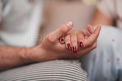 Buy stock photo Cropped shot of an unrecognizable couple holding hands affectionately at home