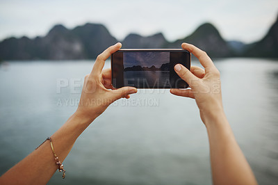 Buy stock photo Shot of a young woman taking pictures of a river in Vietnam with her smartphone