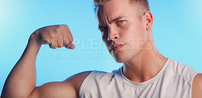 Buy stock photo Studio portrait of a handsome young man flexing his bicep against a blue background