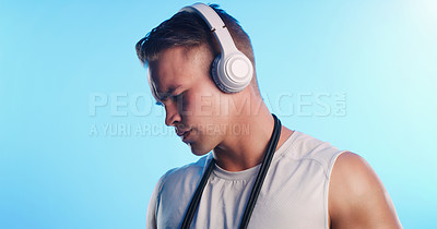 Buy stock photo Studio shot of a young man posing with a skipping rope and headphones against a blue background