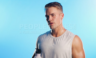 Buy stock photo Studio portrait of a handsome young man posing with a water bottle against a blue background