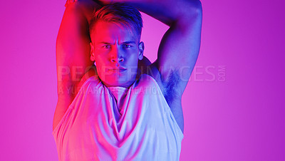Buy stock photo Studio portrait of a handsome young man stretching against a purple background