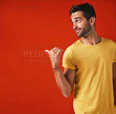 Buy stock photo Studio shot of a handsome young man pointing against a red background