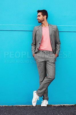 Buy stock photo Shot of a handsome young man posing against a blue wall in the city