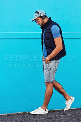 Buy stock photo Shot of a handsome young man listening to music against a blue wall in the city