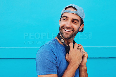 Buy stock photo Shot of a handsome young man listening to music against a blue wall