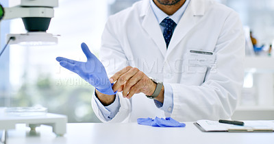 Buy stock photo Closeup shot of an unrecognisable scientist putting on surgical gloves in a lab