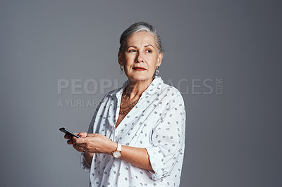 Buy stock photo Studio shot of a senior woman posing against a gray background