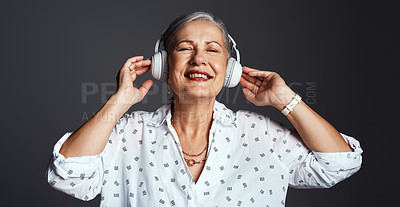 Buy stock photo Studio shot of a senior woman wearing headphones while listening to music against a grey background