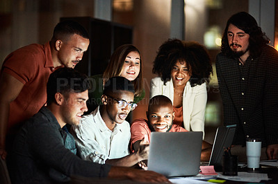 Buy stock photo Shot of a group of designers looking at something on a laptop while working late