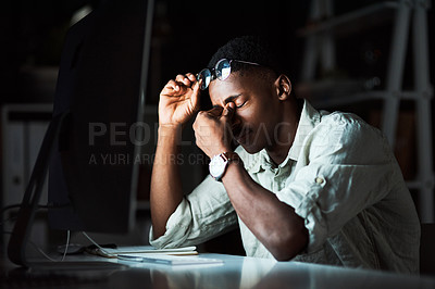 Buy stock photo Shot of a businessman looking tired while working late at the office