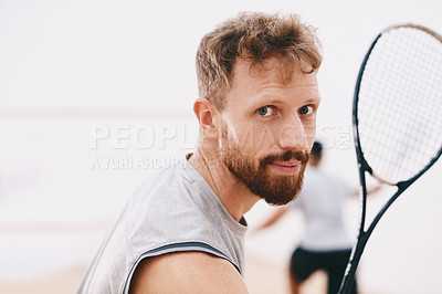 Buy stock photo Portrait of a young man playing a game of squash with his team mate in the background