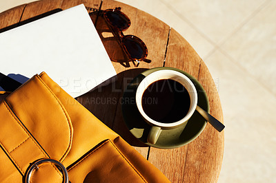 Buy stock photo High angle shot of a cup of coffee and a bag neatly arranged on a coffee table during the day