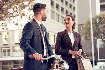 Buy stock photo Shot of two businesspeople having a discussion while walking through the city