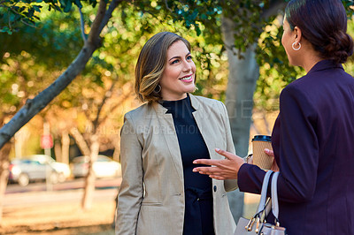 Buy stock photo Shot of two businesswomen having a conversation while standing outdoors