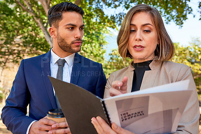Buy stock photo Shot of two businesspeople discussing work while standing outdoors